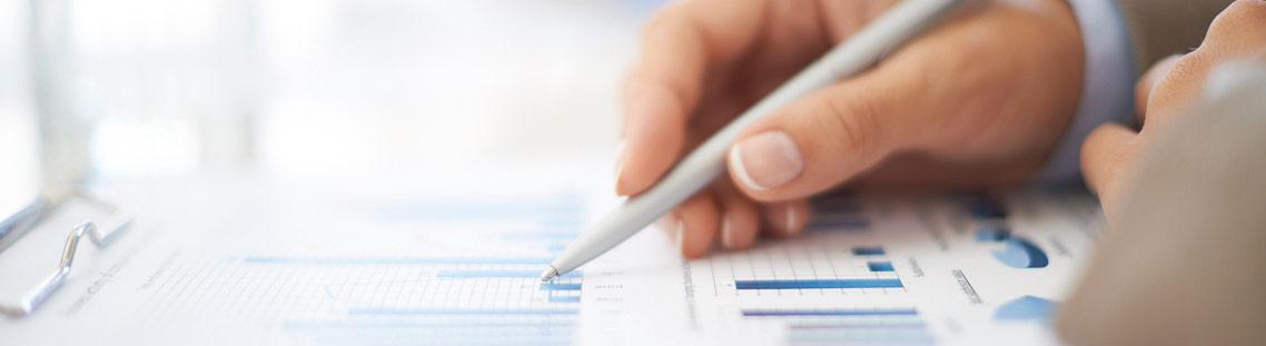 Hand mit Stift macht Notizen auf einem Diagramm
